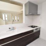 対面キッチンは白を基調とした内装に締まりをつけてくれる色合いです(キッチン)